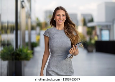 Confident successful business woman smiling with pride, positivity, and enthusiasm on the way to work