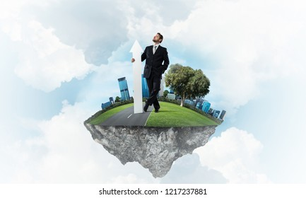 Confident and successful businessman in black suit pointing upside with huge white arrow in his hands while standing on flying island and cloudy skyscape on background.