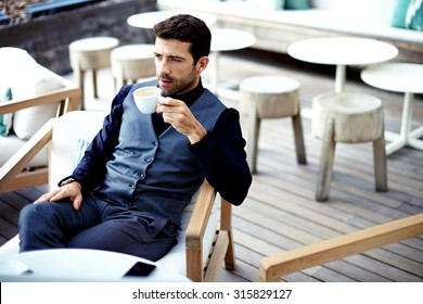 Confident successful businessman in suit enjoying a cup of coffee while having work break lunch in modern restaurant,young intelligent man or entrepreneur relaxing in outdoors cafe looking pensive