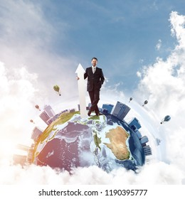Confident and successful businessman in suit pointing upside with huge white arrow in his hands while standing on Earth globe and cloudy sky on background. Elements of this image are furnished by NASA