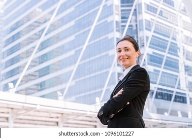 Confident successful businesswoman cross arms in city