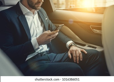 Confident and successful. Close up of young man in full suit holding his smart phone while sitting in the car
