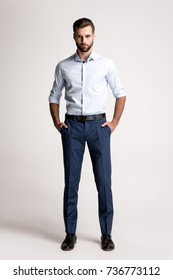 Confident and successful. Full length of handsome young man looking at camera while standing against white background.