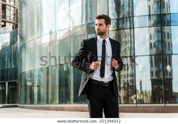 Confident and successful. Handsome young businessman adjusting his jacket and looking away while walking outdoors with office building in the background