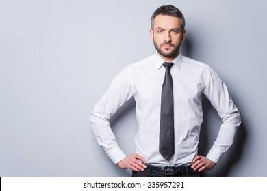Zuversichtlich und erfolgreich. Gewissenswerter reifer Mann in Hemd und Krawatte, der sich die Hände auf der Hüfte hält und die Kamera anschaut, während er auf grauem Hintergrund steht