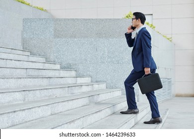 Confident successful Vietnamese entrepreneur walking up the stairs and talking on phone with coworker