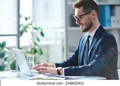 Confident and successful young businessman in elegant suit browsing in the net in front of laptop in office