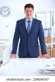 Confident successful young businessman leaning arms on his desk isolated
