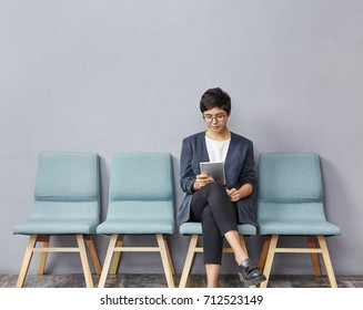 Confident successful young businesswoman with short hairstyle wearing stylish clothes and glasses using digital tablet while waiting for doctor's appointment, sitting on chair in hall at clinic
