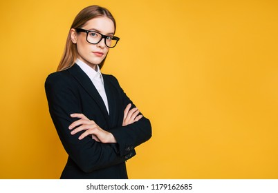 Confident and successfull young business woman in glasses and full suit with crossed arms isolated on yellow background.