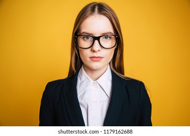 Confident and successfull young business woman in glasses and full suit looks right on camera isolated on yellow background.