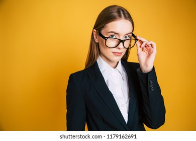 Confident and successfull young business woman in glasses and full suit isolated on yellow background.