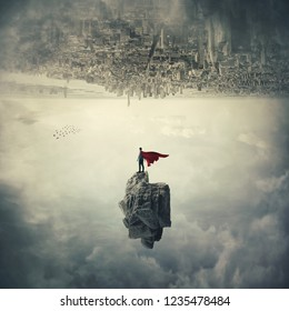 Confident superhero with red cape standing on a levitating stone underneath the cityscape. Imaginary world upside down, mystical scene flying super power.