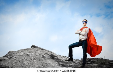 Confident superman in cape and mask standing on ruins