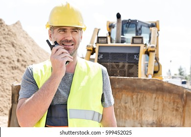 Confident supervisor using walkie-talkie at construction site