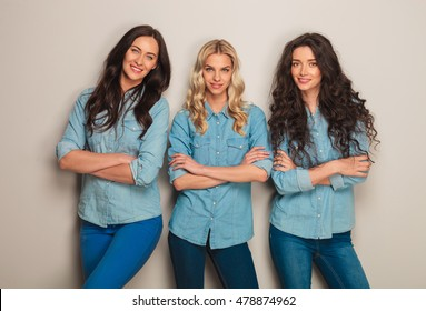 confident team of casual woman standing with hands crossed in studio on grey wall