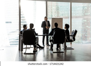 Confident team leader giving flip chart presentation at corporate meeting in modern boardroom with panoramic windows, business people sitting at table, listening to coach mentor explaining strategy