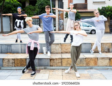 Confident teen boys and girls dancing modern choreography on city street on summer day.