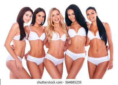 Confident in their perfect bodies. Group of five beautiful women in lingerie bonding to each other and smiling while posing against white background
