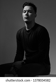 Confident thinking brutal man sitting in blue pullover with fashion watch on the hand on dark shadow background. Closeup portrait. Black and white