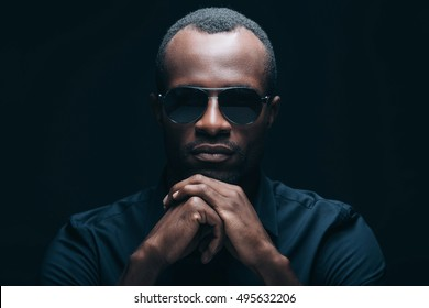 Confident and trendy look. Portrait of handsome young African man in sunglasses leaning his head on hands and looking at camera while being in front of black background