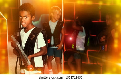 Confident tween  boy standing with laser pistol in dark lasertag room during game with friends
