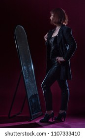 Confident ugly woman wearing black suit stands near mirrow in front of camera on stage with crimson floor and black background