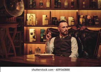 Confident upper class man smoking cigar in gentlemen's club