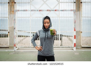 Confident urban sporty woman offering green detox smoothie. Successful fitness nutrition and outdoor workout concept.