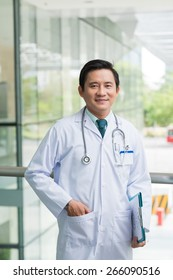 Confident Vietnamese doctor smiling and looking at the camera