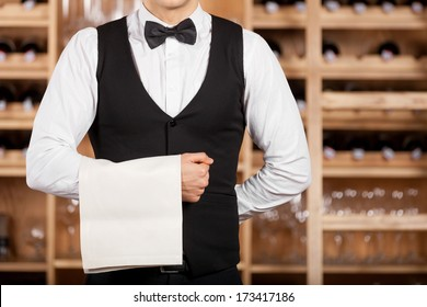 Confident waiter. Cropped image of confident young waiter standing in front of wine shelf and holding a towel on his hand