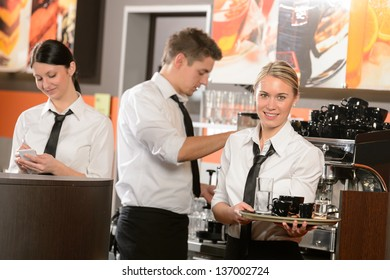 Confident waitresses and waiter working in bar serving drinks