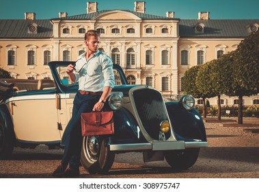 Confident wealthy young man with briefcase near classic convertible