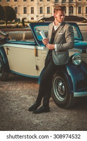Confident wealthy young man with newspaper near classic convertible
