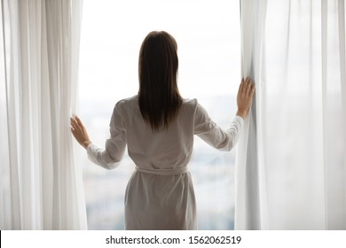 Confident wealthy young woman wear nightgown stand at modern home hotel big window open curtain lace looking outside enjoy good morning new day city view hope dream of future concept, rear back view