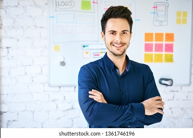 Confident web designer in office looking at camera, standing in front of wall with whiteboard with website wireframe