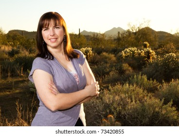 Confident Woman with Arms Crossed Against a Desert Background
