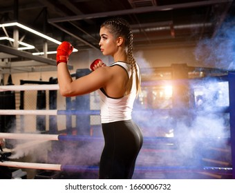 Confident woman boxer wears ptotective gloves, bandages on her wrist. Boxing practice in the gym, ring in the background. Caucasian woman in sportswear is preparing for a boxing fight with opponents