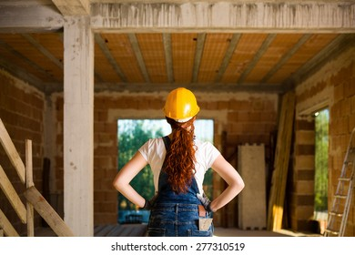 Confident Woman Bricklayer with Overalls and Helmet with Her Hands on Hips