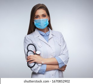 Confident woman doctor wearing medical mask standing with crossed arms. isolated female portrait.