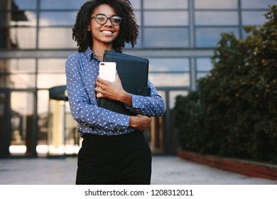 Confident woman in formal clothes holding a smartphone and file looking away smiling. Female executive standing outside office building.