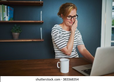 Confident woman at home office talking at the phone while using laptop