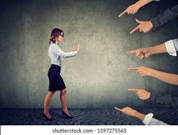 Confident woman keeping hands in stop gesture, trying to defend herself from multiple blaming her people with pointing fingers