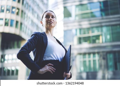 Confident woman looking away while waiting business partner before meeting on publicity area for planning strategy for finance company, female entrepreneur standing on urban setting with folder