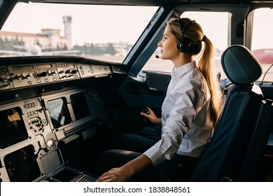 Confident woman pilot flying a commercial aircraft, sitting in cockpit.