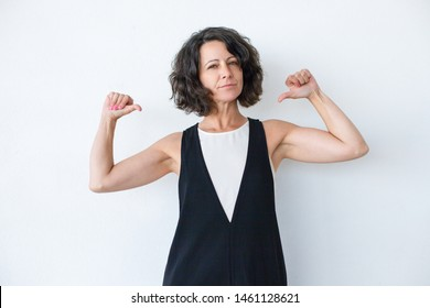 Confident woman pointing at herself. Portrait of attractive brunette middle aged woman looking at camera and pointing with thumbs isolated on grey background. Confidence concept
