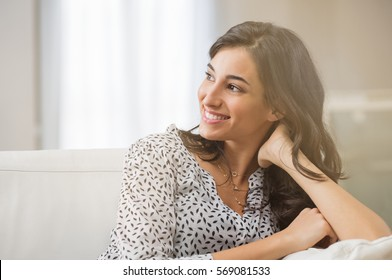 Confident woman relaxing on couch at home. Thoughtful smiling woman sitting on sofa and looking away. Portrait of satisfied girl daydreaming at home.
