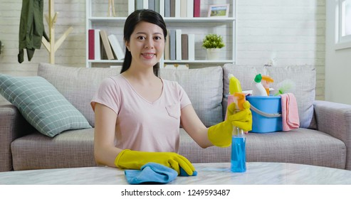 confident woman in rubber protective gloves wiping table holding detergent in the bright living room. beautiful housewife doing housework joyfully indoors in the daytime. lady face camera smiling.