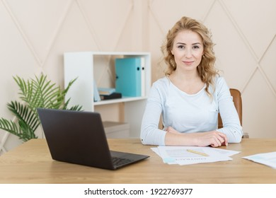 Confident woman sitting in office behind desk with laptop computer and documents, looking at camera. Smiling businesswoman or CEO posing, making headshot picture for company photoshoot