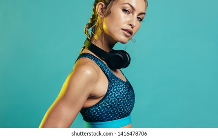 Confident woman in sports bra looking at camera. Caucasian female in sports clothing standing on blue background.
